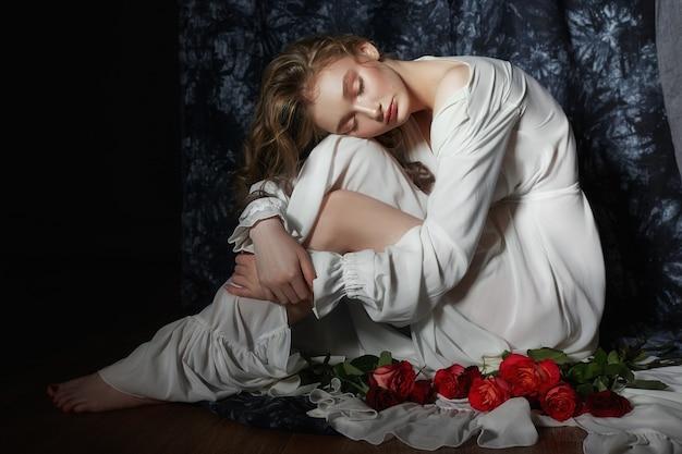 Bella ragazza primaverile è seduta sul pavimento con fiori di rosa nelle sue mani. la donna in abito bianco sta sognando, un'immagine romantica. bionda con i capelli ricci