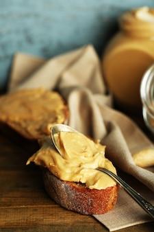 Bella natura morta con burro di arachidi fresco sulla tavola di legno