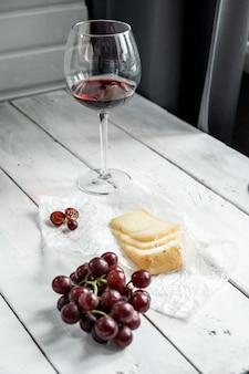 Bella natura morta con un pezzo di formaggio duro e vino rosso in un bicchiere su uno sfondo di legno bianco.