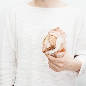 Bella pietra minerale di calcite in mano femminile, sfondo chiaro. quarzo gemma naturale.
