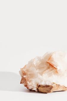 Bella pietra minerale di calcite su sfondo chiaro. pietra preziosa traslucida naturale solida.