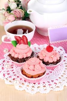 Bellissimi cupcakes alla fragola e tè aromatizzato sul primo piano del tavolo da pranzo