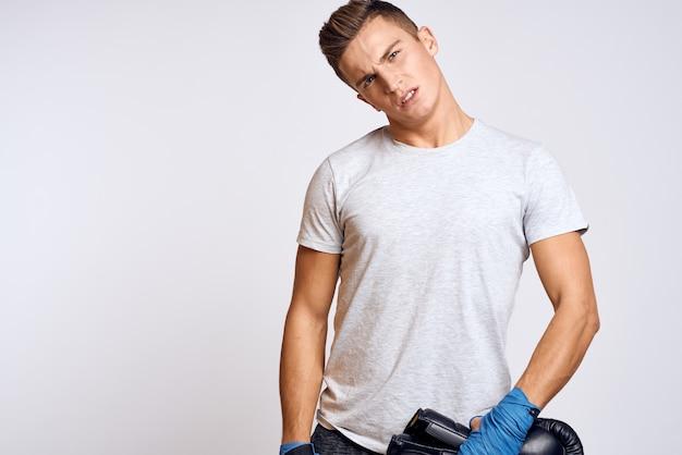 Bellissimo uomo forte con guantoni da boxe e in una maglietta bianca
