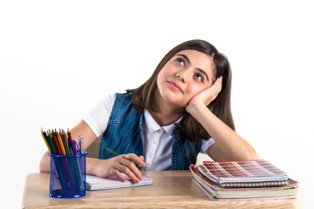 Una bella studentessa si siede alla scrivania e scrive la lettera white