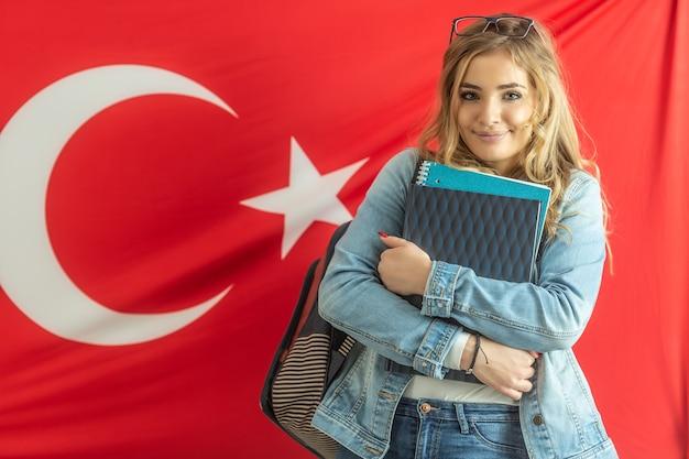 La bella ragazza dello studente sorride tenendo i materiali di studio con una bandiera della turchia dietro di lei.