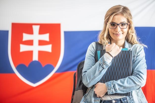 Il bellissimo studente tiene il materiale di studio con la bandiera slovacca nella parte posteriore.