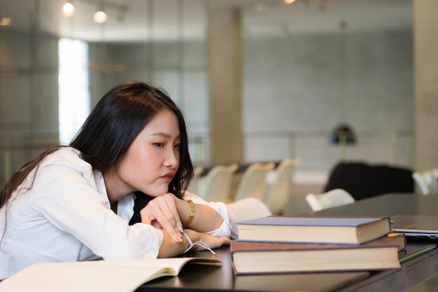 Camicia bianca d'uso del bello studente annoiata mentre leggendo i libri sulla tavola in biblioteca