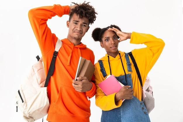 Bellissimi studenti che indossano zaini in possesso di quaderni, isolati su muro bianco