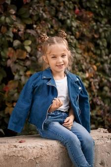 Una bella ragazza bionda alla moda con una giacca blu si siede su un blocco di cemento. bambina di 7 anni con un sorriso su uno sfondo di foglie
