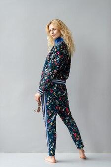 Bello modello biondo alla moda in vestito colorato che propone nello studio