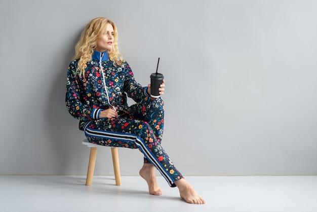 Bello modello biondo alla moda in vestito colorato che si siede sulla piccola sedia
