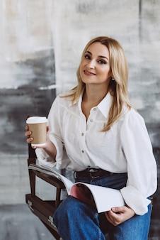 Bella donna bionda alla moda in abiti casual in denim e una camicetta bianca con maniche voluminose con una rivista e un caffè in mano. messa a fuoco selettiva morbida.