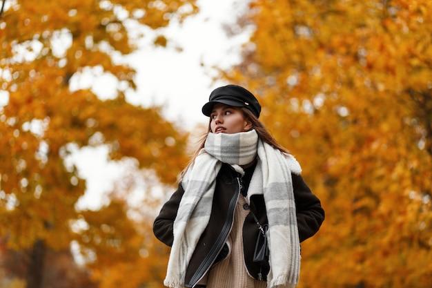 Bella giovane donna carina alla moda in una giacca marrone alla moda in un elegante cappello nero con una sciarpa calda vintage passeggiate nel parco d'autunno. modello di moda ragazza europea attraente gode di una passeggiata all'aperto.