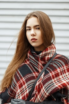 Bella donna alla moda alla moda con una sciarpa rossa vicino a una parete di legno