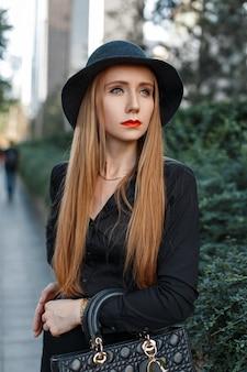 Bella ragazza alla moda in un cappello in piedi vicino a cespugli verdi