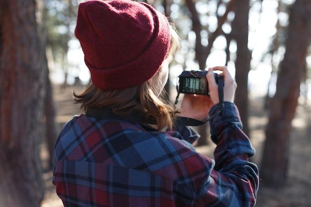 Bella ragazza alla moda che tiene una macchina fotografica nella foresta. condizioni selvagge