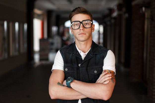 Uomo bello alla moda hipster in occhiali vintage con tatuaggi