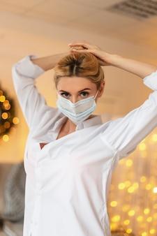 Bella donna infermiera alla moda con maschera medica protettiva in camicia bianca alla moda con luce gialla bokeh al chiuso. ragazza operaia medica
