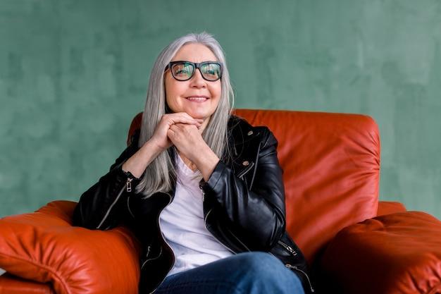 Bella donna senior elegante con lunghi capelli lisci grigi, indossando occhiali e giacca di pelle nera, seduto in comoda poltrona sofr rossa su sfondo verde
