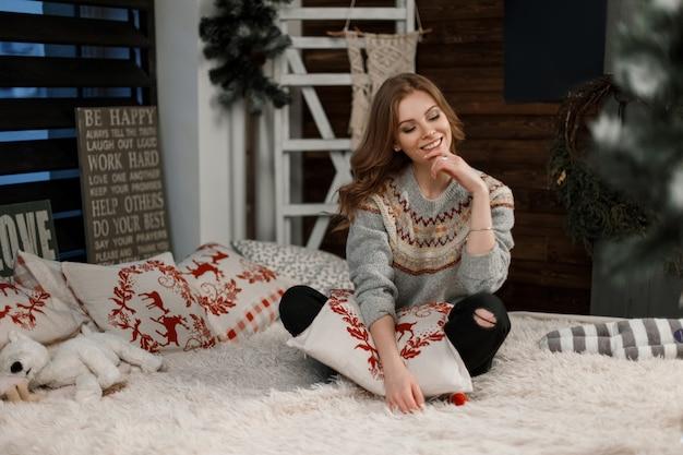 Bella donna alla moda in maglione vintage alla moda con un cuscino seduto sul letto