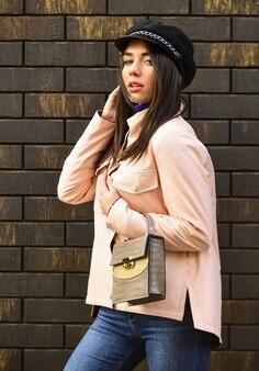 Bella donna alla moda che cammina in giacca rosa. indossando cappelli alla moda. stile di strada. tendenza primavera autunno. donna alla moda in giacca rosa. stagione fredda. look autunnale o primaverile.