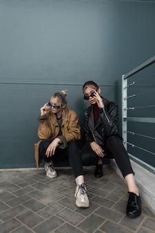 Belle giovani amiche alla moda in abiti alla moda con giacche di pelle, jeans e scarpe da ginnastica sedute e in posa vicino a un edificio moderno