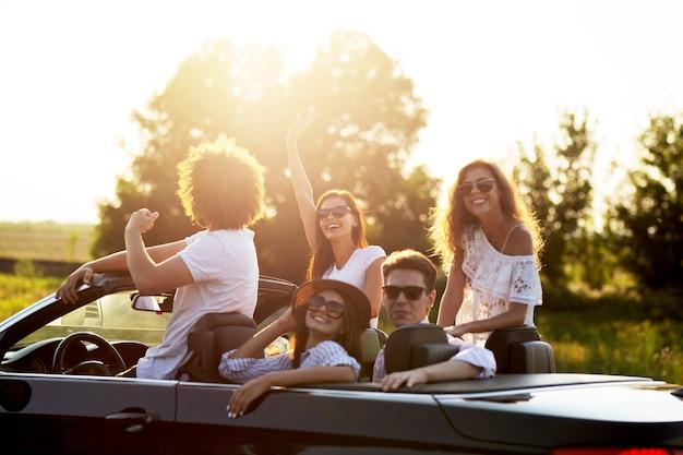 Belle ragazze e ragazzi alla moda in occhiali da sole sono seduti e ridono in una cabriolet nera in una giornata di sole. .