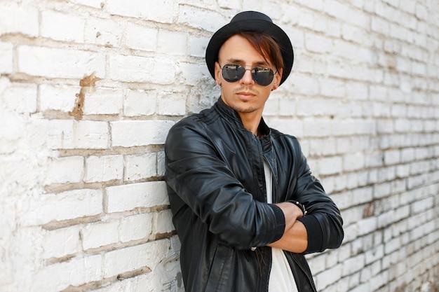Bello giovane alla moda in occhiali da sole in un cappello alla moda e giacca di pelle nera in posa vicino al muro di mattoni