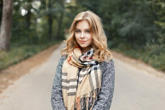 Bella giovane donna alla moda in una sciarpa calda e cappotto che cammina lungo la strada nel parco