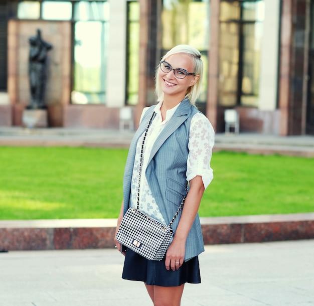 Bella giovane donna alla moda con gli occhiali su una strada