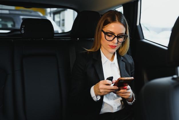 Bella imprenditrice di successo parla sul suo telefono cellulare in un sedile posteriore di un'auto