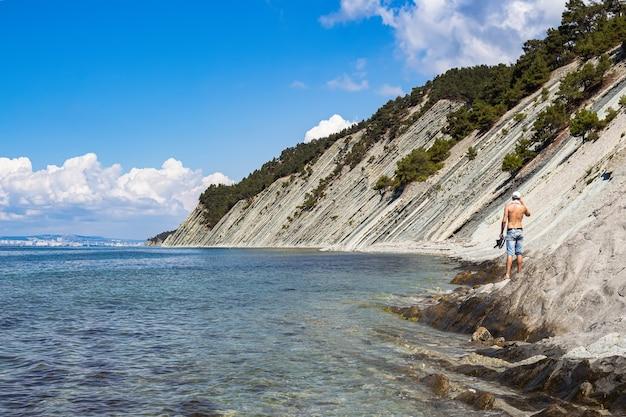 Bellissimo paesaggio estivo, cielo azzurro con nuvole, ripide scogliere e un ragazzo in piedi sulla riva. gelendzhik, russia, costa del mar nero