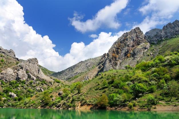 Bellissimo paesaggio estivo, lago con acque azzurre situato tra le montagne rocciose
