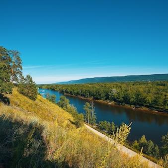 Bellissimo paesaggio estivo in una giornata di sole. ampio fiume tra colline, intorno ad alberi, boschi, vegetazione.