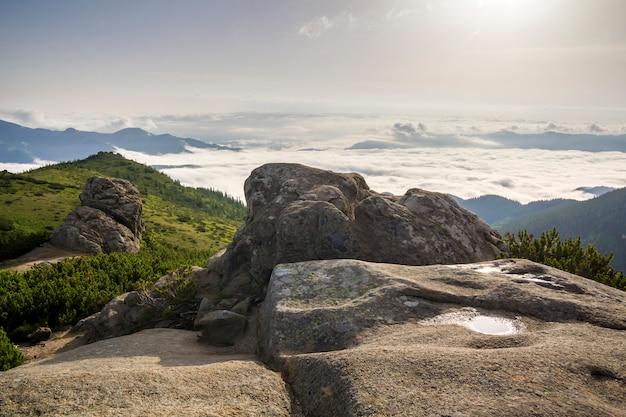Panorama di montagna bella estate all'alba. il masso enorme con la pozza dell'acqua piovana sulla cima verde della montagna rocciosa sopra della valle nebbiosa ha riempito di nuvole gonfie bianche e di chiaro cielo blu dello spazio della copia.