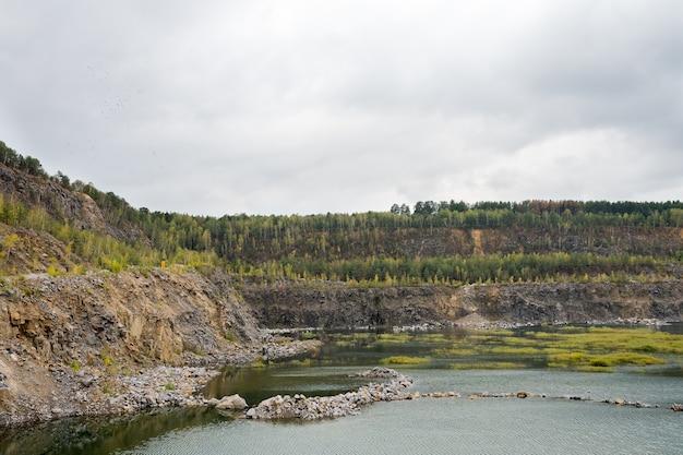 Lago di cava bella estate nelle scogliere con cielo blu nuvoloso