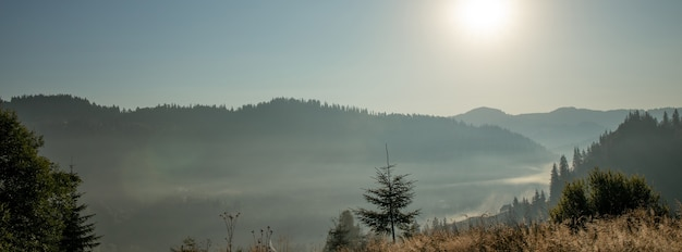 Bellissima alba in montagna con nebbia bianca sottostante