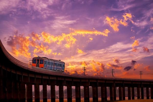 Bellissimo cielo all'alba o al tramonto sul treno che si muove sul ponte ferroviario in thailandia