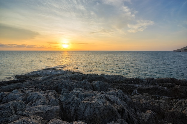 Il bello tramonto sopra il mare calmo con calcare oscilla la montagna al capo tailandia di promthep