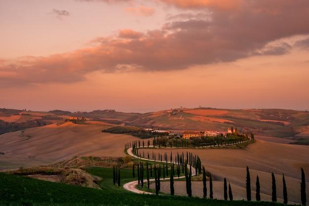 Bel tramonto su colline e cipressi dalla strada, paesaggi della toscana