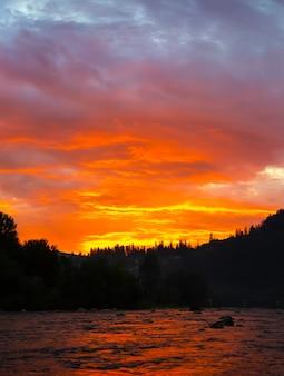 Bel tramonto in montagna. colori e nuvole viola del cielo. incredibile riflesso nel fiume. concetto di viaggio. natura perfetta di sera.