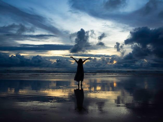 Bellissimo sfondo di paesaggio marino del cielo al tramonto con silhouette di donna felice che alza le mani sulla spiaggia di sabbia bagnata con riflesso, mare scuro e il vasto sfondo del cielo