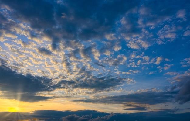 Bel tramonto con il sole al tramonto che rompe le nuvole
