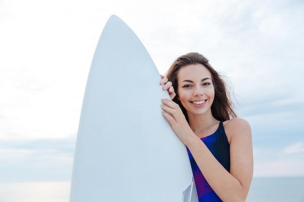 Bella ragazza adolescente surfista in piedi con la tavola da surf in spiaggia