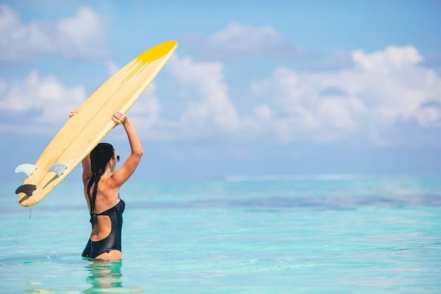 Bella donna surfista pronta a navigare nel mare turchese su stand up paddle board in vacanza esotica