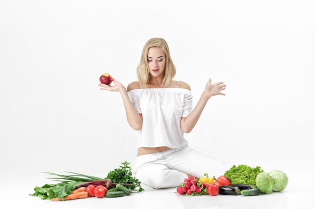 Bella donna bionda sorpresa in vestiti bianchi e un sacco di verdure fresche su uno sfondo bianco. la ragazza sta mangiando la nettarina