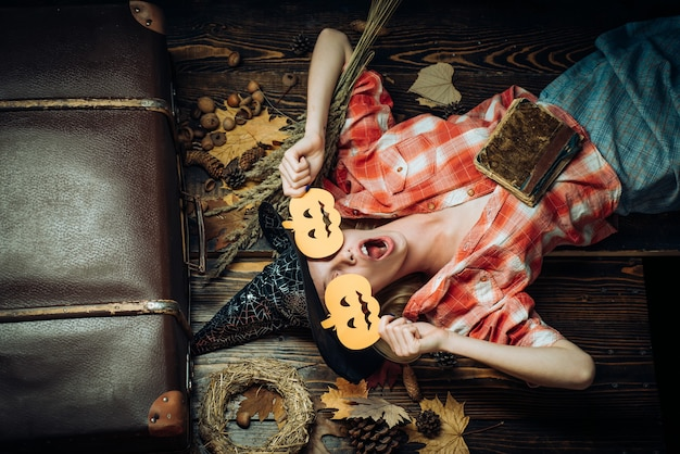 Bella donna sorpresa in cappello e costume delle streghe - mostrando i prodotti. ritratto di donna di halloween. piuttosto giovane donna in costume da strega. espressione divertente. gente felice. divertirsi.