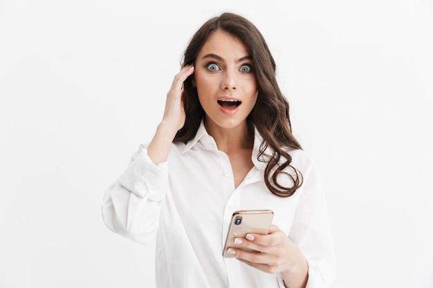 Bella giovane donna sorpresa con lunghi capelli castani ricci che indossa una camicia bianca in piedi isolata sul muro bianco, usando il telefono cellulare