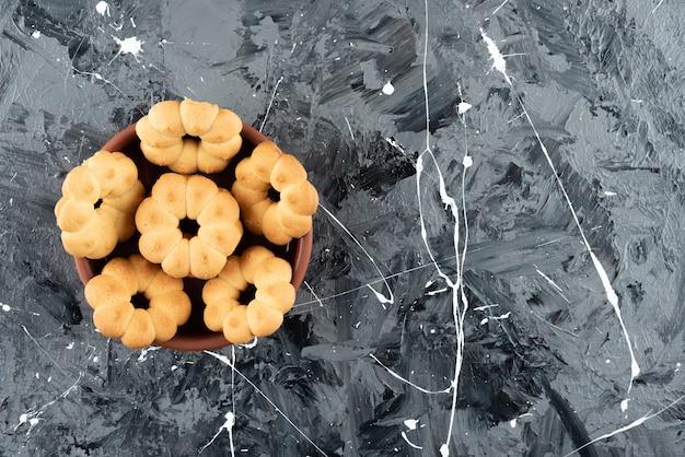 Bellissimi biscotti dolci per il tè in una ciotola di argilla su una superficie di marmo
