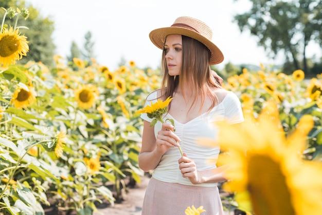 Bella ragazza dolce con un cappello di paglia che cammina su un campo di girasoli sorridenti